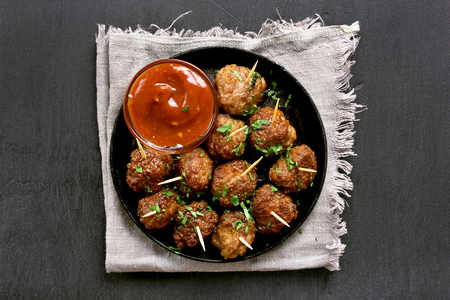 Homemade meatballs with tomato sauce on black stone background
