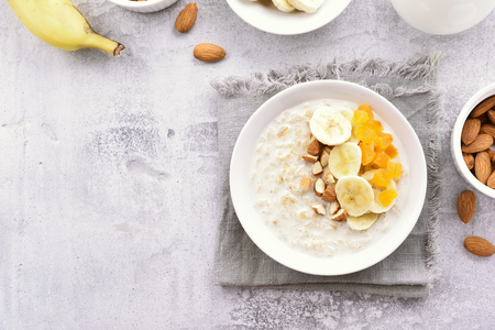 Diet breakfast oats porridge with banana slices, nuts and dried apricot on stone background with copy space. Healthy natural food. Top view, flat lay Stock Photo