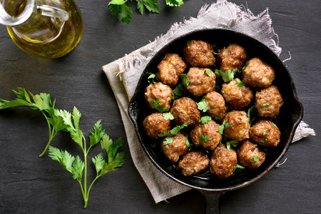 Meatballs in frying pan on black stone background. Top view, flat lay