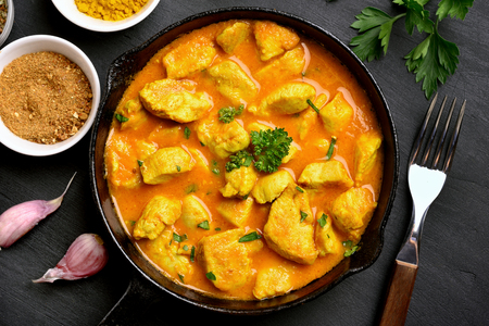 Tasty chicken curry in frying pan on dark stone background. Top view, flat lay