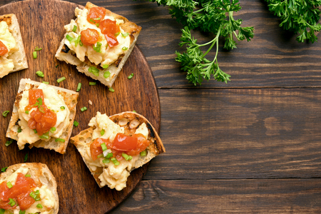 Omelet, scrambled eggs on toasted bread with green onion and tomato over wooden background with copy space. Top view, flat lay