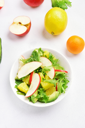 Natural organic food. Fruit vegetable salad with red apples, avocado, orange slices on white stone background. Healthy diet food. Top view.