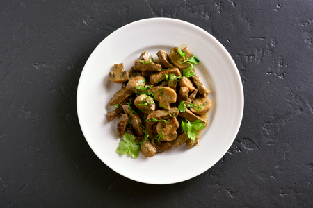 Tasty beef stroganoff with mushrooms on white plate over black stone background. Top view, flat lay