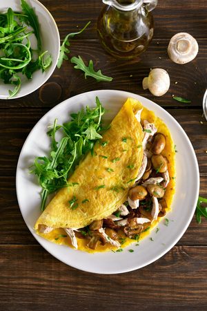 Omelette with mushrooms, chicken meat, greens on wooden table. Healthy food for breakfast. Top view, flat lay Foto de archivo