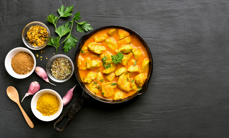 Chicken curry on black stone background with copy space. Top view, flat lay