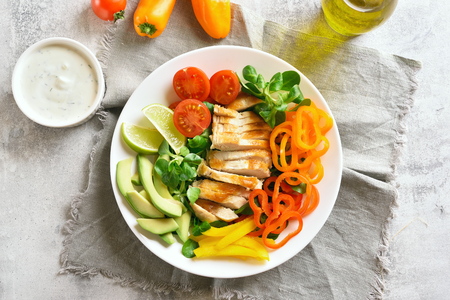 Tasty vegetable salad with grilled chicken breast on stone table. Top view, flat lay