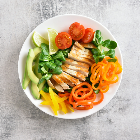 Healthy vegetable salad with grilled chicken breast on stone background. Top view, flat lay Standard-Bild