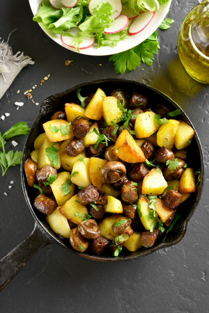 Roasted potatoes with mushroom and sausage in frying pan over black stone background. Top view, flat lay