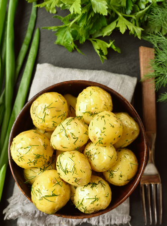 Vegetarian vegan or natural organic food concept. Tasty new boiled potatoes with dill in bowl. Top view