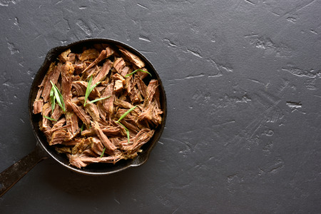 Slow cooked pulled beef for sandwiches in frying pan on black stone background with copy space. Top view