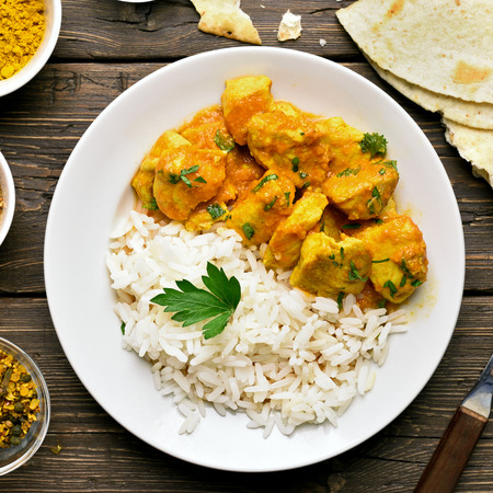 Chicken curry with rice on plate over wooden background. Top view, flat lay