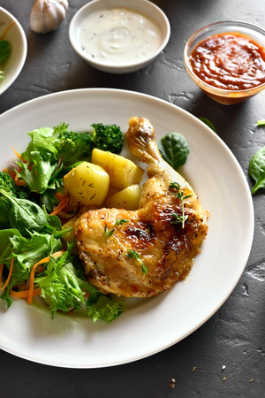 Roasted chicken leg with potato and green salad on black stone background. Dish for dinner.