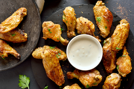 Baked chicken wings with sauce on black background. Top view, flat lay Stock Photo