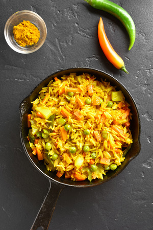 Vegetable pilaf in frying pan over black stone background. Vegetarian vegan food. Top view, flat lay