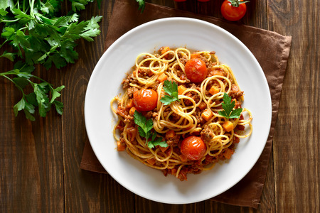 Tasty spaghetti with minced meat and vegetables on wooden background. Top view, flat lay 免版税图像
