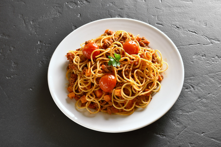 Delicious spaghetti with minced meat, cherry tomatoes, carrot on black stone table. Close up view