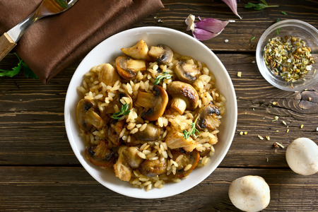 Risotto with mushrooms and pieces of chicken meat on wooden table. Top view, flat lay Stock Photo