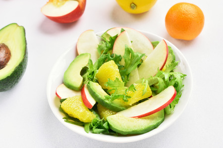 Salad with red apples, avocado, orange slices on white stone background. Healthy diet food. Natural food Stok Fotoğraf