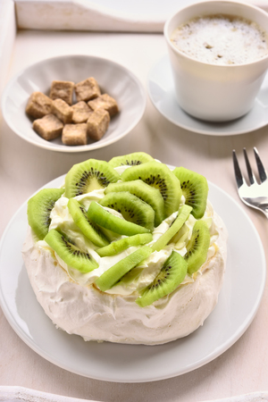 Dessert Pavlova meringue cake with kiwi slices anf cup of coffee.