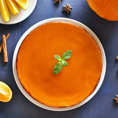 Close up of pumpkin orange pie on blue stone background. Traditional autumn dish from pumpkin. Healthy vegetarian food. Top view, flat lay