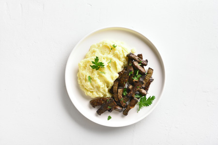Roasted beef liver with mashed potatoes on white plate over stone background with copy space. Top view, flat lay