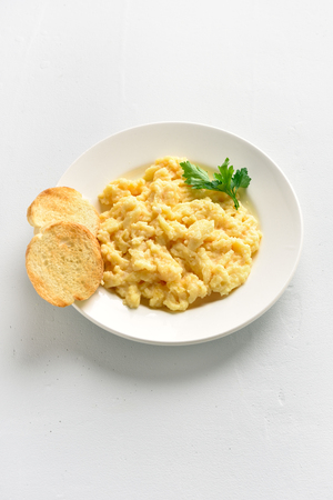 Scrambled eggs on plate over white stone background with copy space. Tasty omelette.
