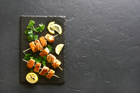 Fish salmon kebab. Barbecue salmon skewers on slate board over black stone background with copy space. Top view, flat lay