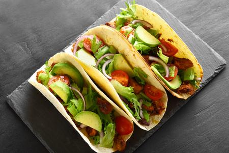 Tacos con carne y verduras en tablero de pizarra sobre fondo de piedra negra.