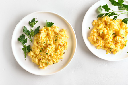 Scrambled eggs on plate over white stone background. Top view, flat lay 스톡 콘텐츠