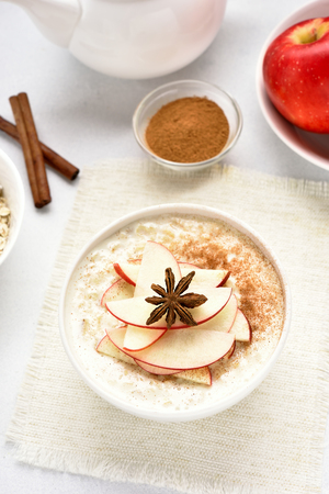 Oatmeal porridge with red apple slices and cinnamon. Healthy diet breakfast concept. Top view