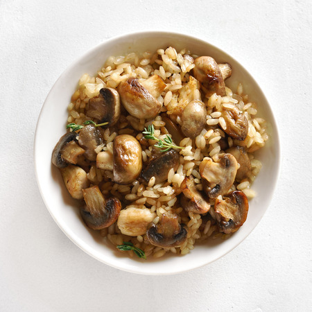 Close up of risotto with mushrooms and pieces of chicken meat in bowl over white stone background. Top view, flat lay