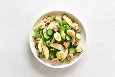Thunfischsalat mit Gurkenscheiben, Avocado, rotem Apfel und Eiern in Schüssel über weißem Steinhintergrund. Gesunde Ernährung. Ansicht von oben, flach
