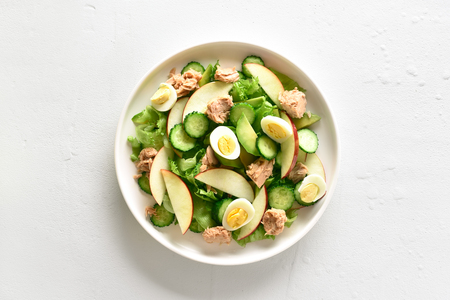 Tuna salad with slices of cucumber, avocado, red apple and eggs in bowl over white stone background. Healthy diet food. Top view, flat lay