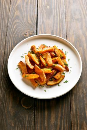 Oven baked pumpkin slices on white plate over wooden background. Healthy vegetarian, vegan food. Reklamní fotografie