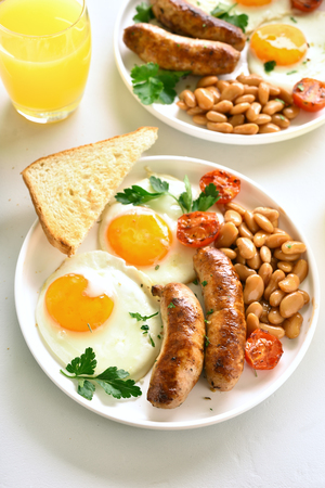 English breakfast with fried eggs, sausages, beans, tomatoes, greens on plate over white stone table