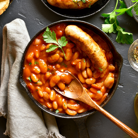 Close up of baked white beans in tomato sauce with sausage in frying pan over black stone background. Top view, flat lay Reklamní fotografie