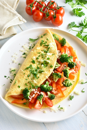Omelet with tomatoes, red bell pepper and broccoli on light wooden table. Healthy diet food for breakfast. Tasty morning food.