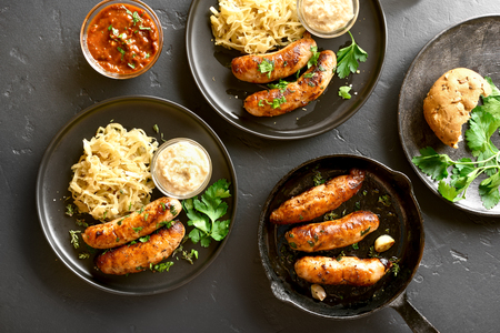 Grilled sausages with sauerkraut and horseradish on plate over black stone background. Top view, flat lay Reklamní fotografie - 123048281