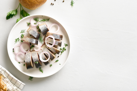 Marinated herring with spice, herbs and onion on plate on white stone background with copy space. Seafood with healthy unsaturated fats, Omega 3. Top view, flat lay