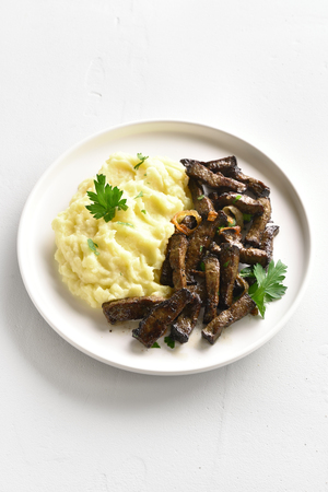 Mashed potatoes with roasted beef liver on white plate over stone background with copy space.