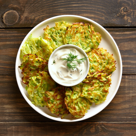 Close up of zucchini fritters with sauce on white plate over wooden background. Vegetarian food. Top view, flat lay