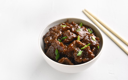 Mongolian beef in bowl on white stone background. Food in asian style