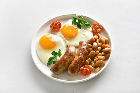 Fried eggs, sausages, beans, tomatoes, greens on plate over white stone background Stock Photo