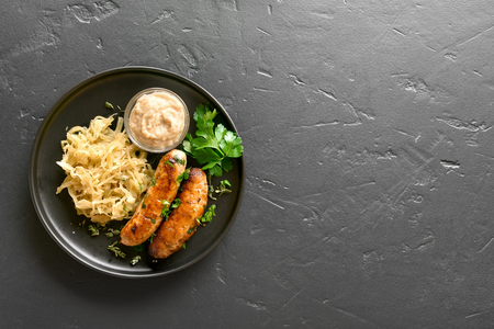 Stewed sauerkraut with grilled sausages on plate over black stone background with copy space. Top view, flat lay Stok Fotoğraf