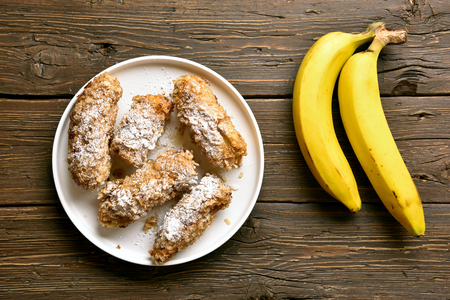 Tasty deep fried bananas on plate over wooden background. Dessert from pan fried bananas in asian style. Top view, flat lay