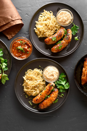 Stewed sauerkraut with grilled sausages and horseradish on plate over black stone background. Top view, flat lay