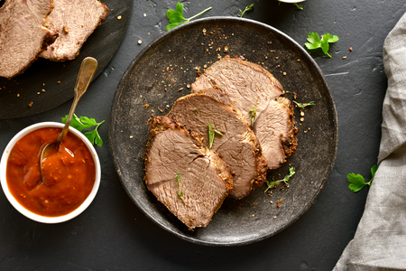 Sliced grilled roast beef on plate. Top view, flat lay Stock Photo