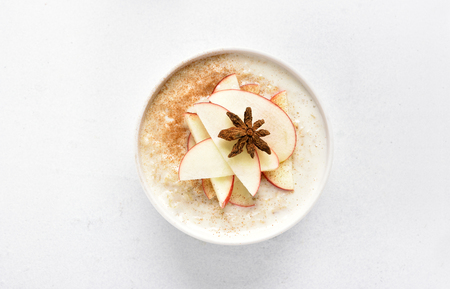 Dish for healthy diet breakfast. Oats porridge with red apple slices and cinnamon on white stone background. Top view, flat lay
