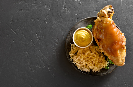 Baked pork knuckle (eisbein) with braised cabbage (sauerkraut) and mustard on black stone background with copy space. Top view, flat lay