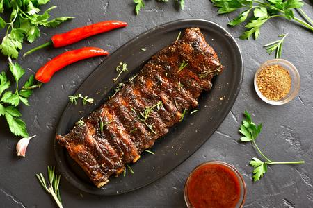 Costine di maiale alla griglia su piastra su sfondo di pietra nera. Carne gustosa alla griglia. Vista dall'alto, posizione piatta Archivio Fotografico